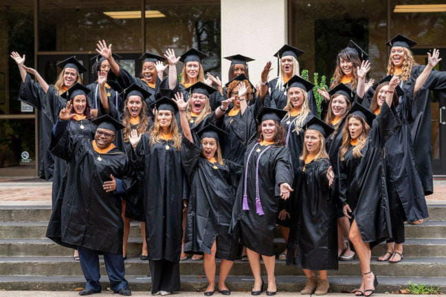 Nursing students pose in academic regalia